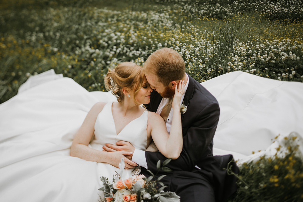 Bride & Groom laying in flower