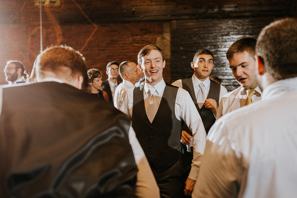groom smiles at reception