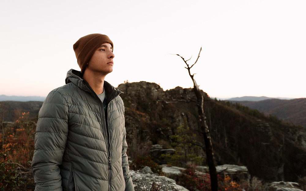 Grey coat and brown beanie in the mountains