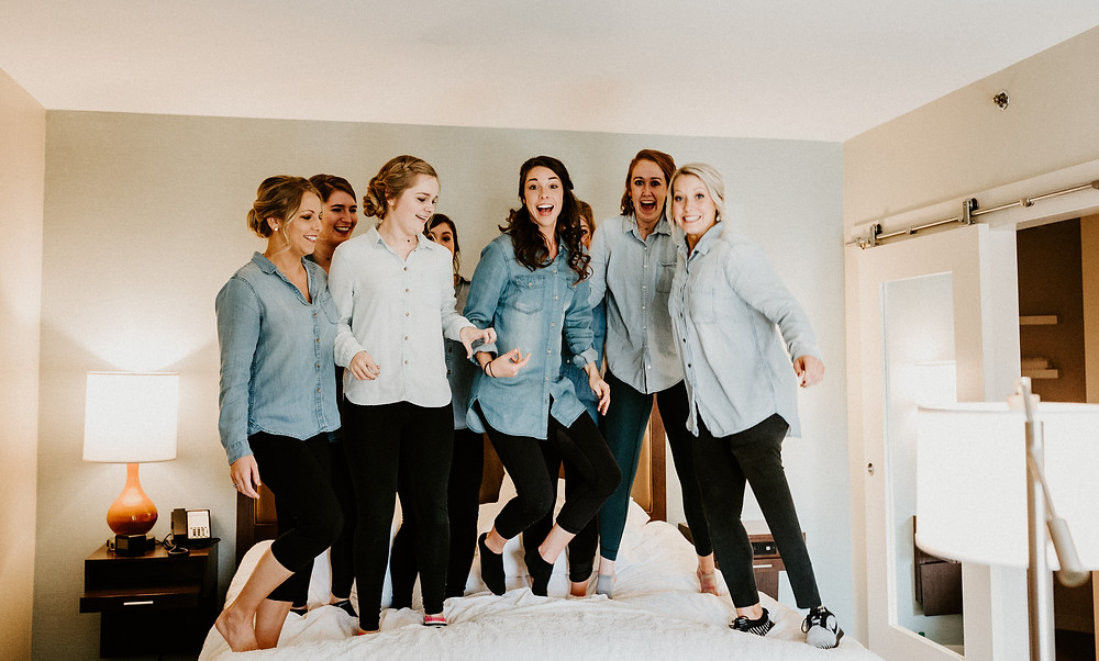 Bridemaids jumping on bed