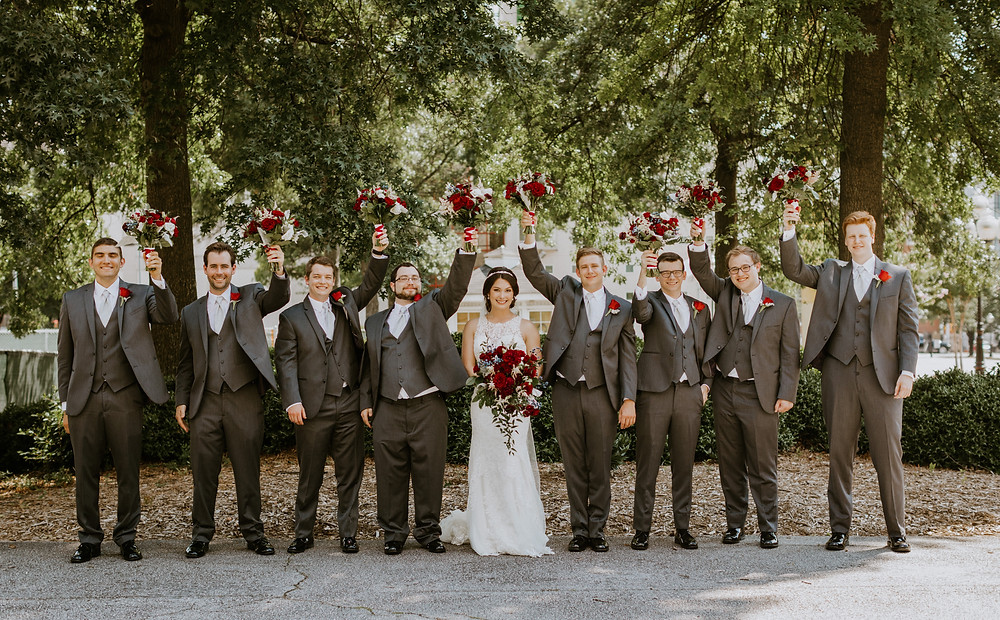 bride and groomsmen hold flowers