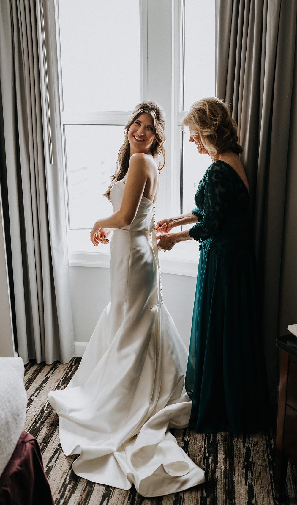 Mom zipping us wedding dress