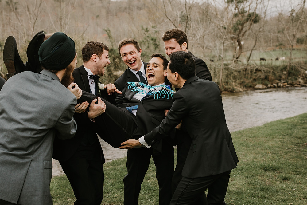 groomsmen hold groom