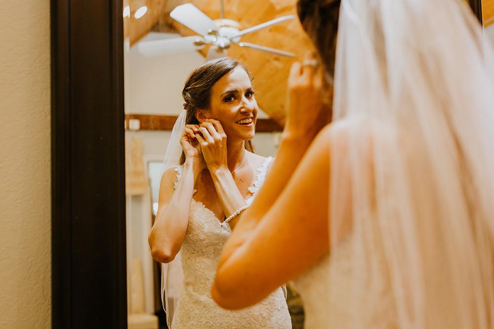 Bride putting on earings