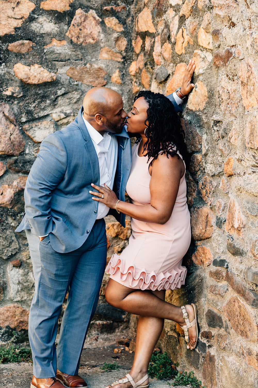 Romantic engagement picture against stone wall