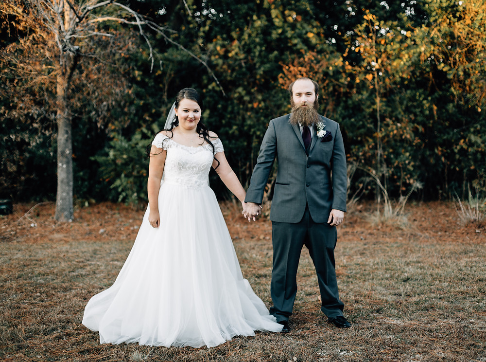 Bride and groom portraits holding hands facing camera