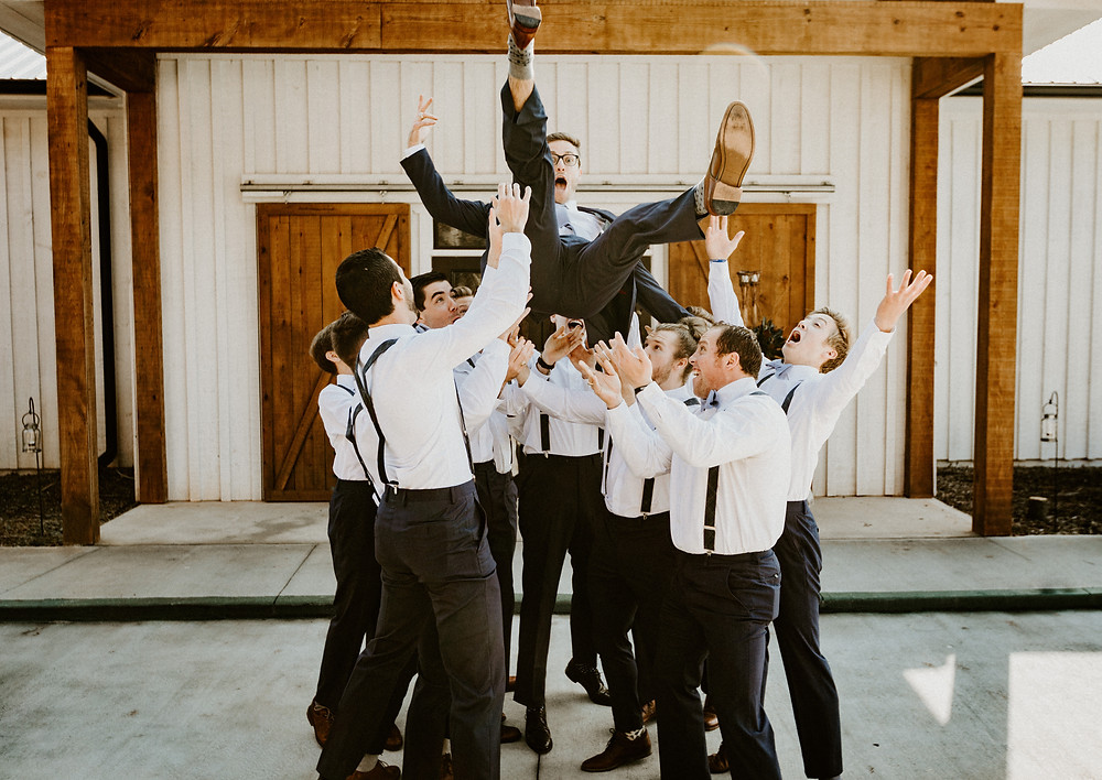 Groomsmen throwing groom Portraits