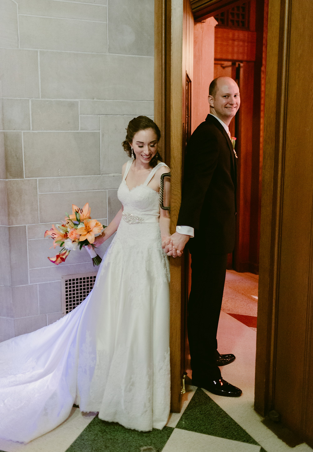 Holding hands behind door before ceremony
