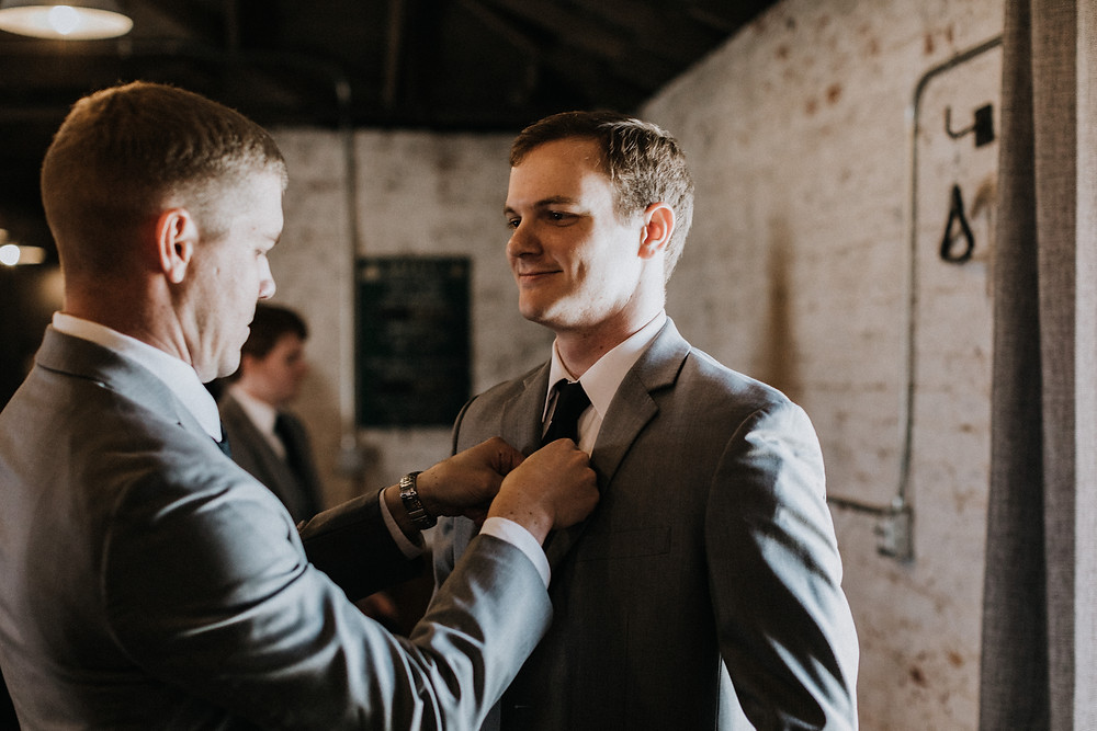Brother helps with groom's tie