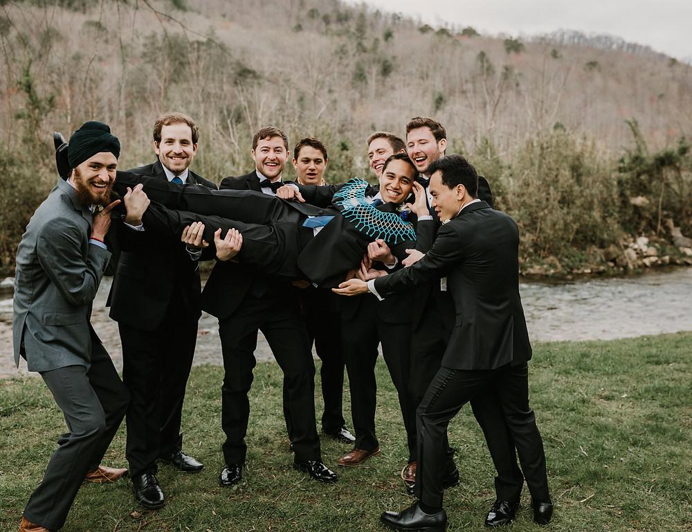groomsmen picking up groom