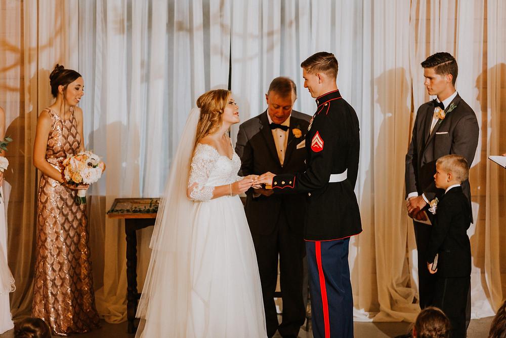 bride puts ring on groom