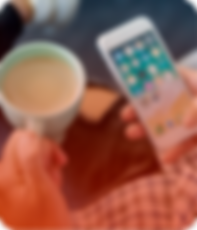 Pessoa tomando café e utilizando um aparelho de celular
