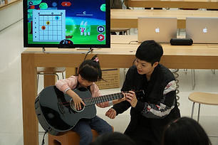 Cantopop star and guitarist Eman Lam shows a young child how to use Monster Chords to learn guitar playing