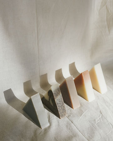 A styled image of five unpackaged triangle soaps diagonally lined up in front of a linen backdrop