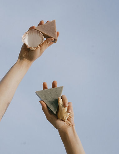 Two hands against a blue sky holding triangle soaps and seashells in their hands