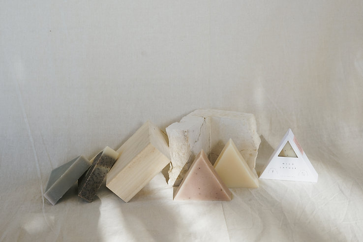 A landscape styled image of five triangle soaps leaning against some wood and stone