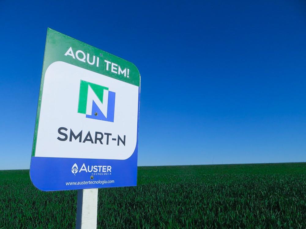 Placa azul, verde e branca escrito aqui tem Smart-N em frente a uma lavoura de trigo
