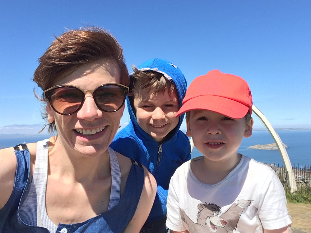 Picture of Linda with her two sons. Sunny day, on top of a windy hill.