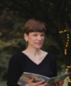 Image of Linda holding open a ceremony script. There are fairy lights in the background.
