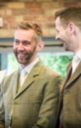 Image of two men in tweed kilt jackets. Both are laughing, one is looking at his husband, who is loo