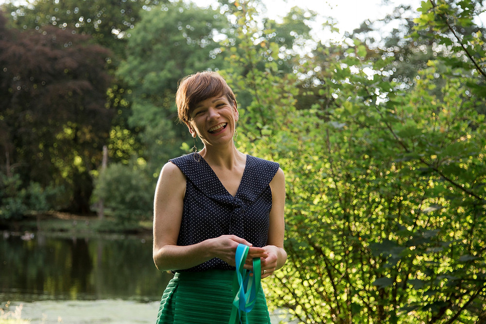 Picture of Linda, laughing and looking at the camera. There are trees in the background and a pond to her left. She is holding some green and blue ribbons.