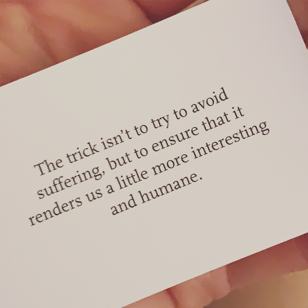 """A hand holding a card that reads, """"The trick isn't to avoid suffering, but to ensure that it renders us a little more interesting and humane""""."""