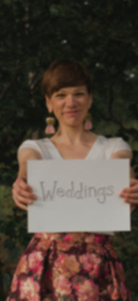 "Picture of Linda looking at the camera and smiling, holding forwards a sign that says ""weddings'"