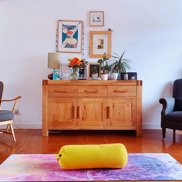 A yoga mat and yellow bolster are in the foreground, with a sideboard covered in plants, flowers and a lamp in the background. There are some pictures on the wall.