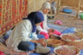 Women extracting argan kernel from fruit