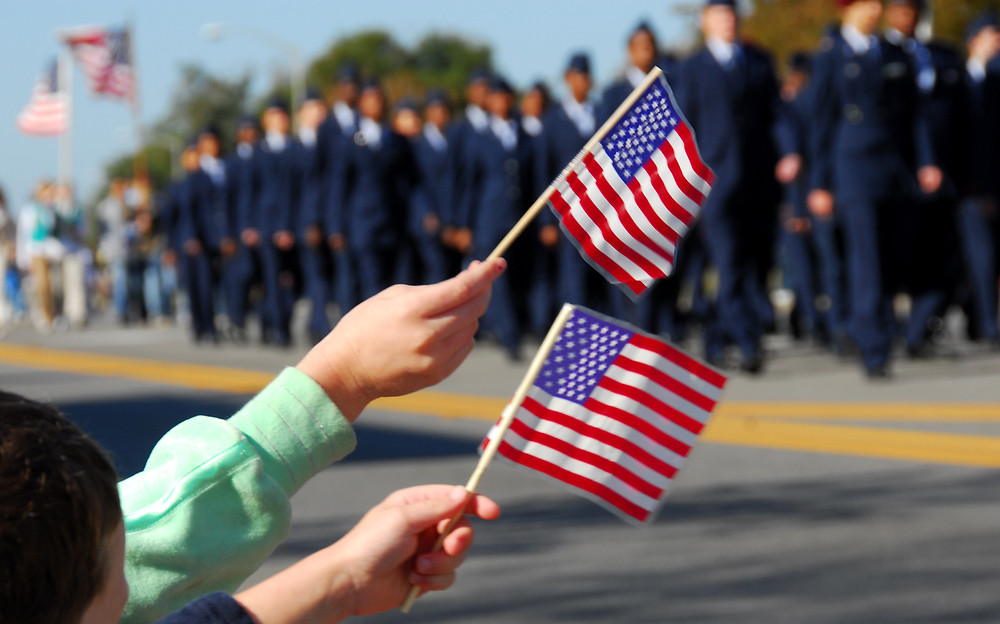 Kids waving flags as military members march by in a parade