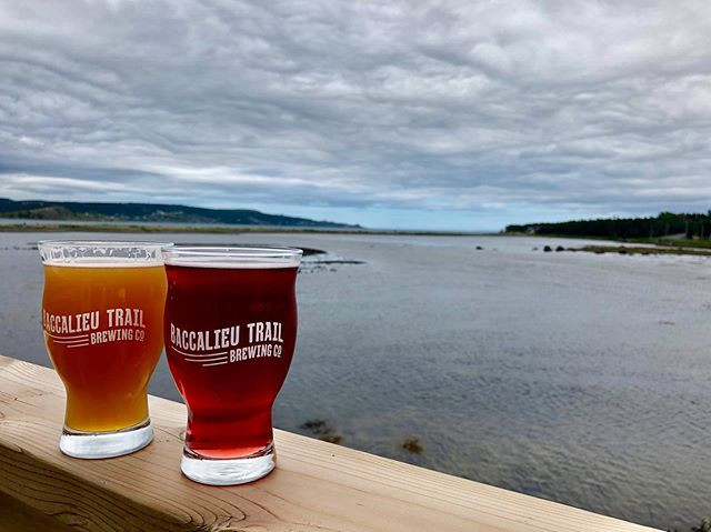 two cold beers places on the deck at Baccalieu Trail Brewing co with ocean behind