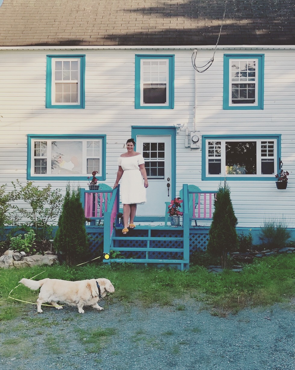 woman in front of teal and white saltbox style home with dog walking in front.