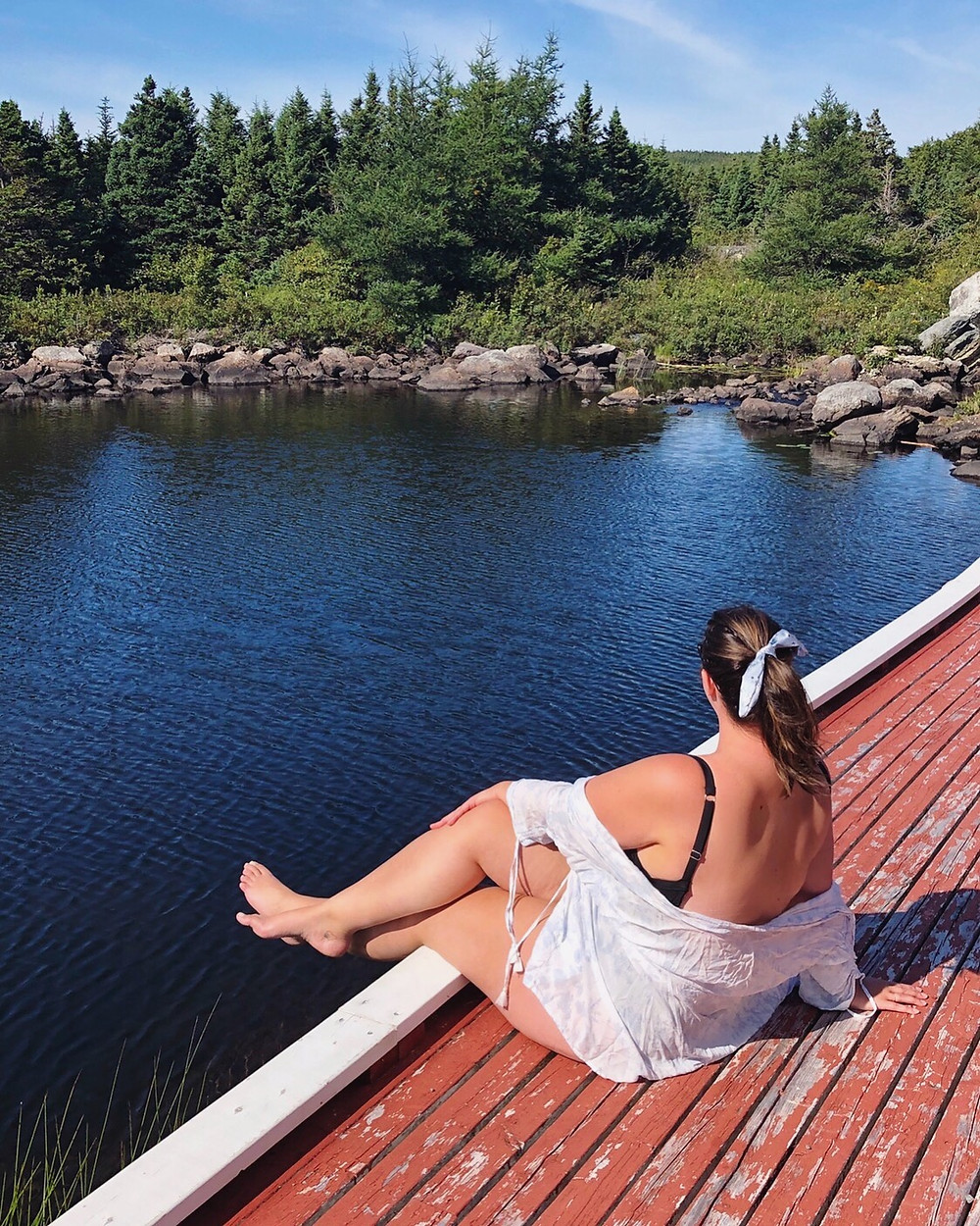 woman sitting on the edge of a dock in her bathing suit about to go swimming