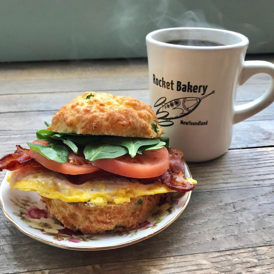rocket bakery breakfast sandwich with a steaming hot coffee