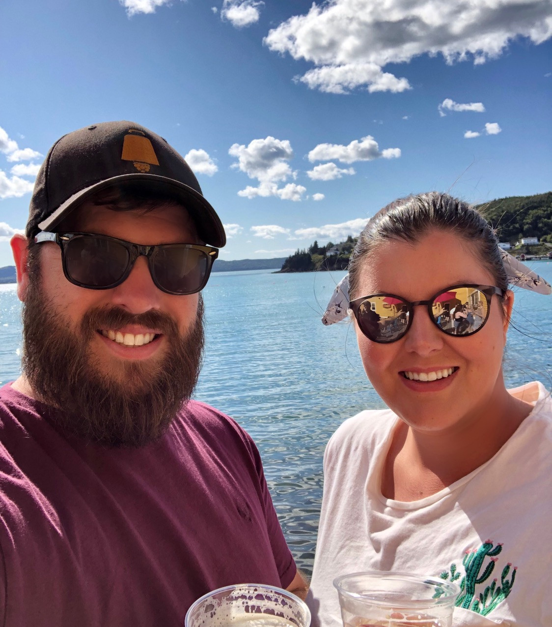 husband and wife smiling, enjoying the ocean views at Dildo Brewery