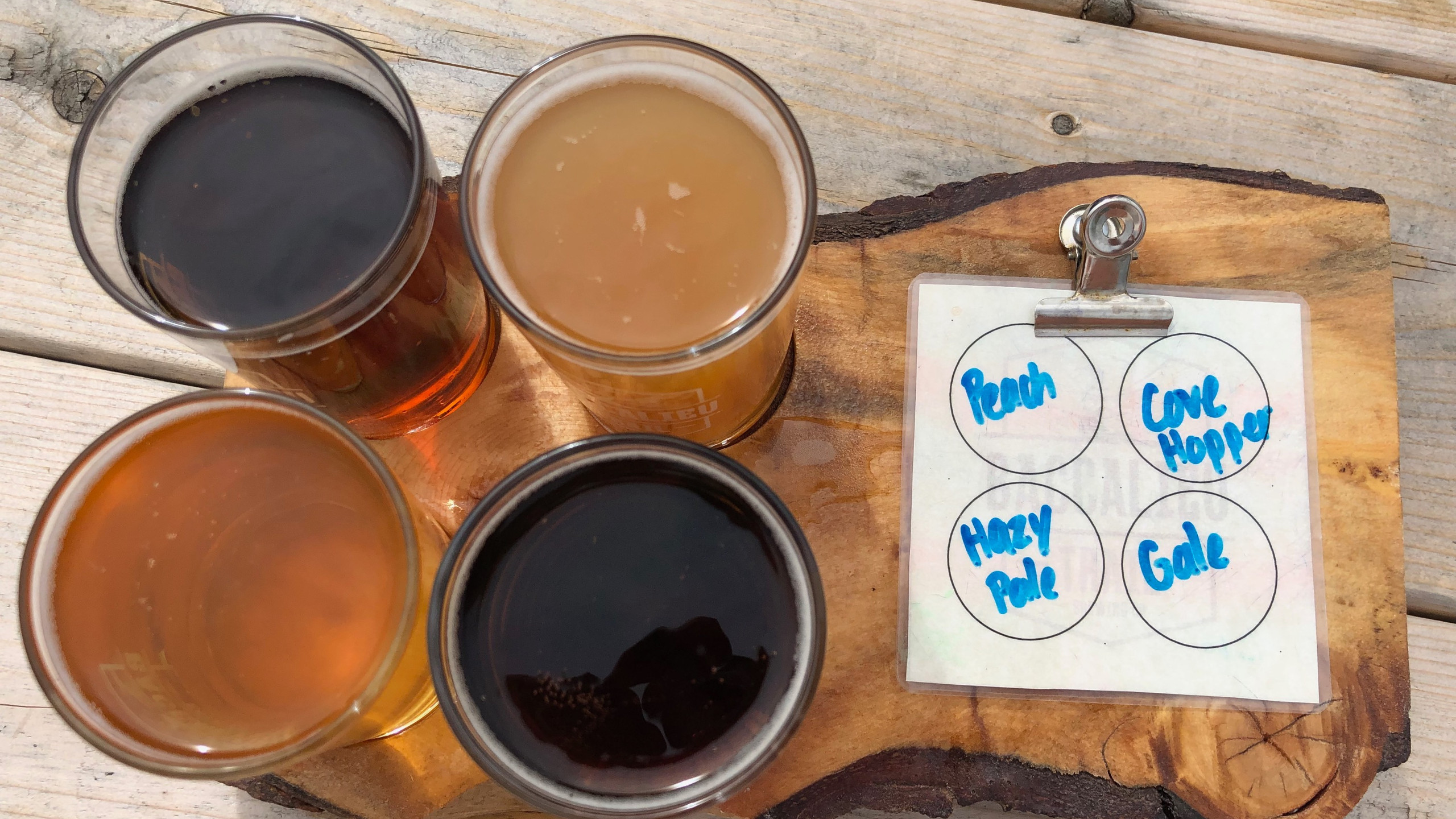 4 sample beers on a piece of sliced wood for a flight at a brewery
