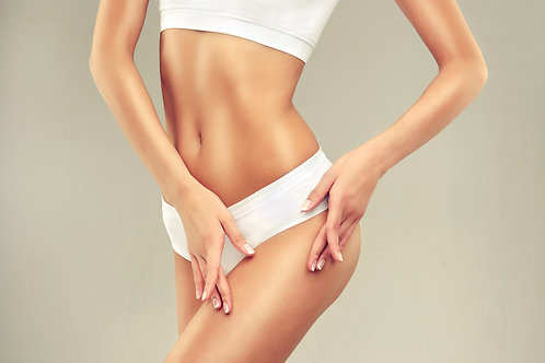 Toned woman in white bathing suit holding her hands on her hip in front of her.