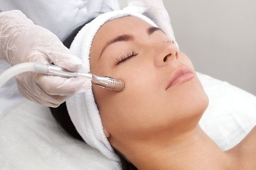Woman laying on white table receiving a microdermabrasion treatment
