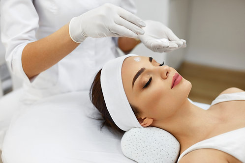 Woman laying on white table with a white headband getting a beta clarity acne peel.