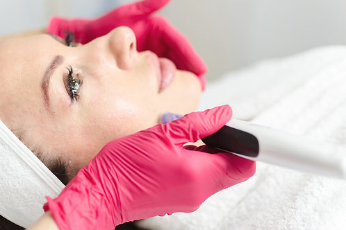 Nurse in pink latex gloves performing Micropen Microneedling on a woman's face.