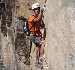 un alpiniste escaladant la via ferrata du Roc del Quer en Andorre avec un guide de montagne