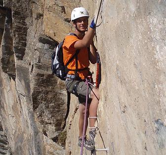 alpinista escalando la via ferrata del roc del quer en andorra con un guia de montaña