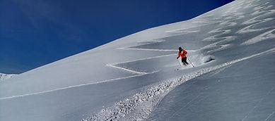 un skieur descend dans la neige poudreuse entre les traçes de montée et de descente accompagné d'un guide de montagne privé
