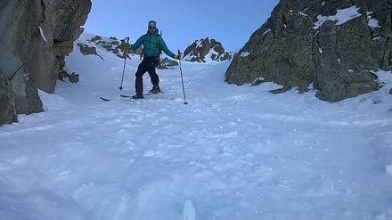 un montañero esquiando una canal en Arcalis con un guia de montaña
