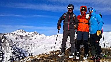 Trois skieurs au sommet du Cap d'Entor en Andorre accompagnés de leur guide de montagne