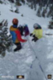 Un guide de montagne forme ses élèves en train de faire des ancrages dans la neige
