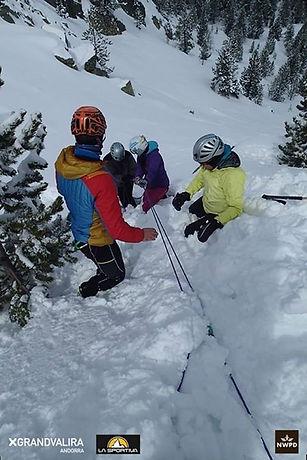 Un guia de montaña formando a sus alumnos haciendo un anclage de fortuna en la nieve