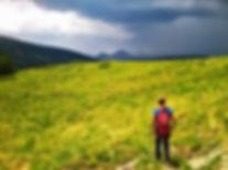 una montañera practicando el senderismo por el valle de incles en verano con un guia de montaña