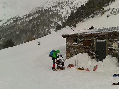un alpiniste enlève ses raquettes pour entrer dans un refuge de montagne à la vall del riu en Andorre
