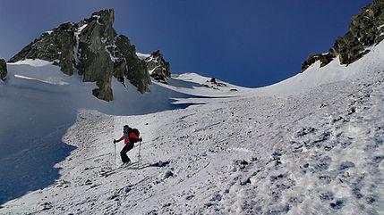 Una esquiadora descendiendo con esquis una canal de nieve virgen con su guia de montaña en grandvalira